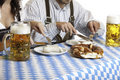 Oktoberfest couple having beer stein and meal Stock Photos