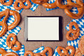 Oktoberfest german beer festival  background with digital tablet and pretzel. Royalty Free Stock Photo