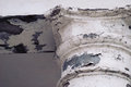 Old abandoned cracked column capital with peel of the paint. Fragment
