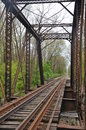 Old abandoned iron railroad bridge tracks and support girders on an crossing a wooded stream Royalty Free Stock Photo