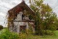 Old abandoned and overgrown house an with vines that are showing the colors of autum Royalty Free Stock Photography