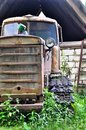 Old abandoned tracked tractor in green grass of small village Royalty Free Stock Image