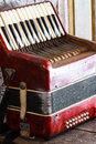 Old accordion located on the red wood tables Royalty Free Stock Photos