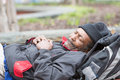 Old african american homeless man sleeping outside during the day Stock Photography