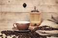 Old aged still life on coffee beans, cup and coffee grinder Royalty Free Stock Photo