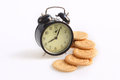 Old alarm clock and cookies on white background Stock Photography