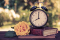 Old alarm clock on a pile of books. Vintage tinting. Royalty Free Stock Photo