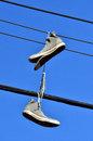 An old all star shoes hanged on electric line Stock Image