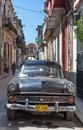 Old american car in a shabby street in havana sidelined with decaying buildings these cars still use after many decades have Royalty Free Stock Photos