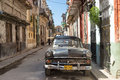 Old american car in a shabby street in havana sidelined with decaying buildings these cars still use after many decades have Stock Photos