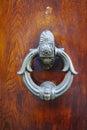 Old ancient door knocker on wooden door Royalty Free Stock Photo