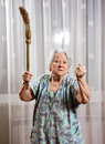 Old angry woman threatening with a broom at home Stock Image