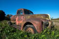 Old antique farm vintage truck an sits in the weeds under a blue sky the machine slowly turns to rust Stock Images