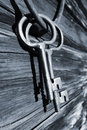Old antique keys and ring against old bard wall two giant hanging from a barn th century blue toning concept Stock Photo