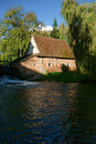 Old antique mill with weeping willow on a river masonry flour and beautiful mature trees reflection in the water scenic in Royalty Free Stock Photo