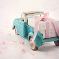 Old antique toy truck carrying a gift box with pink ribbon on romantic lace background and flower petals Stock Images