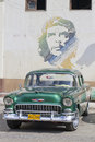 Old aqua classic car and che cuban with mural of guevara painted above Stock Photo