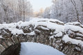 Old arch bridge over the river in the wintery landscape Stock Photos