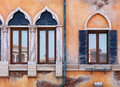 Old arched windows of venetian house yellow wall antique building with rustic texture Royalty Free Stock Photo