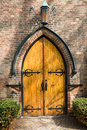 Old arched wooden door double in a face brick building facade in gothic style with a herringbone patterned paved path and neat Royalty Free Stock Photo