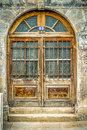 Old arched wooden doorway with windows and iron grating in montreal Royalty Free Stock Image