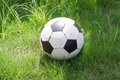 Old ball football on a green grass Stock Photography