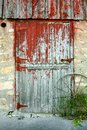 Old barn door a rustic with peeling red paint stone walls and an antique wagon wheel Stock Photography