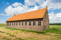 Old barn in a rural landscape with a blue sky and white clouds dutch of brick masonry an orange tile roof the summer season Royalty Free Stock Photo