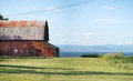 Old barn on shoreline an with cedar shingle roof and green grass a with mountain like hills in background Stock Photo