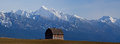 The old barn with the snowy mission mountains this image of in cultivated field in background was taken near ronan montana Royalty Free Stock Photo