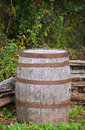 Old barrel vertical a shot of an and rustic sitting in the corner of an wooden fence Royalty Free Stock Image