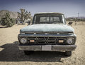 Old battered faded car in the desert an dirty paint automobile sits on sand california mojave Stock Photos