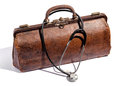 Old battered leather doctors bag and stethoscope closed brown for instruments equipment with a draped over the top on white Royalty Free Stock Photos