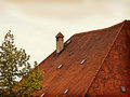 Old Bavarian roof with red tiles and chimney Royalty Free Stock Photo