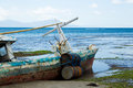 An old beached fishing boat surrounded with seagrass in timor leste Royalty Free Stock Photos
