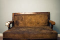 Old beaten up sofa antique worn out with a damaged arm rest Royalty Free Stock Image