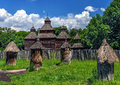 Old beehives and old church wooden on a meadow near the village in folk arts museum pirogovo kiev ukraine Stock Photos