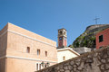 Old bell tower behind houses and buildings inside the fort in the city of corfu in greece Stock Photo