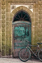 Old bicycle in front of a weathered door morocco seen Stock Photos