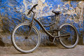 Old bicycle leaning on a weathered wall in morocco Stock Photos