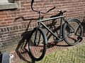 An old Bicycle standing next to a stone wall. City landscape of Amsterdam