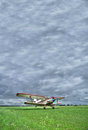 Old biplane takeoff under the storm from grass rougn airstrip into stormy clouds Royalty Free Stock Photo