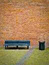 Old black bench trashcan front red brick wall Stock Photography