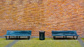 Old black bench and trashcan in front of a red brick wall Stock Photography