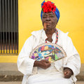 Old black lady smoking a cuban cigar in havana huge and wearing typical dress with afrocuban religious necklaces Stock Image