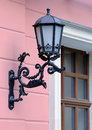 Old black metal wall streetlight antique victorian outdoor lamp Royalty Free Stock Images
