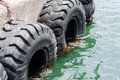 Old black tires used as bumpers at dock Royalty Free Stock Photo