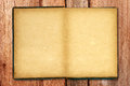 Old blank open notebook on wooden background texture Royalty Free Stock Images