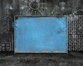 Old blue blank weathered noticeboard with sun city buildings doo doodles on dark mottled concrete wall and floor background Royalty Free Stock Photos