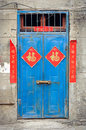 Old blue Chinese door with good fortune posters Royalty Free Stock Photo